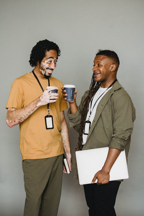 Cheerful African American male living with psoriasis wearing casual clothes talking to content black coworker while chatting and drinking hot takeaway coffee together