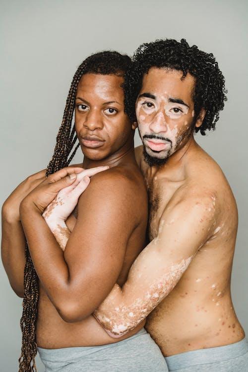 Shirtless black homosexual men embracing in studio