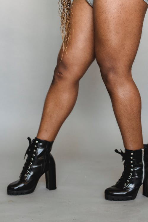 Crop faceless black person with bare legs in leather boots