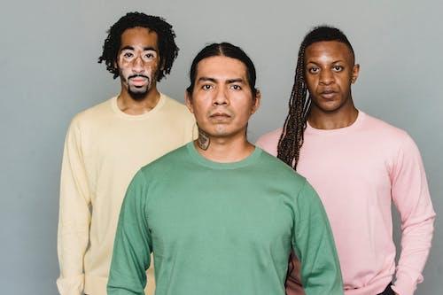 Serious multiethnic men standing in studio