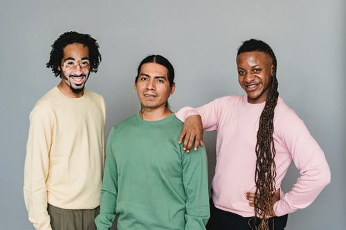 Optimistic black man living with psoriasis standing near content American Indian and homosexual black male against gray wall in photo studio
