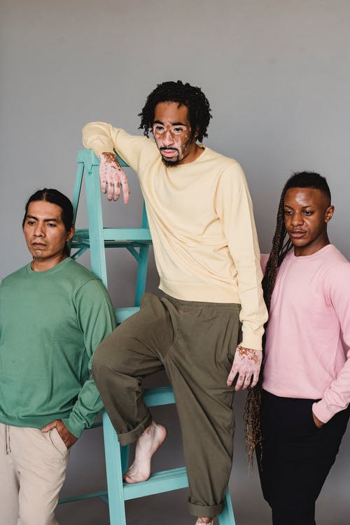 Contemplative black man with vitiligo standing on ladder near thoughtful American Indian and black male friends during photo session in studio