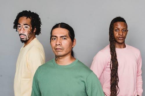 Contemplative multiethnic men standing in studio