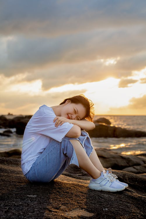 Woman in White Hoodie and Blue Denim Jeans Sitting on Seashore