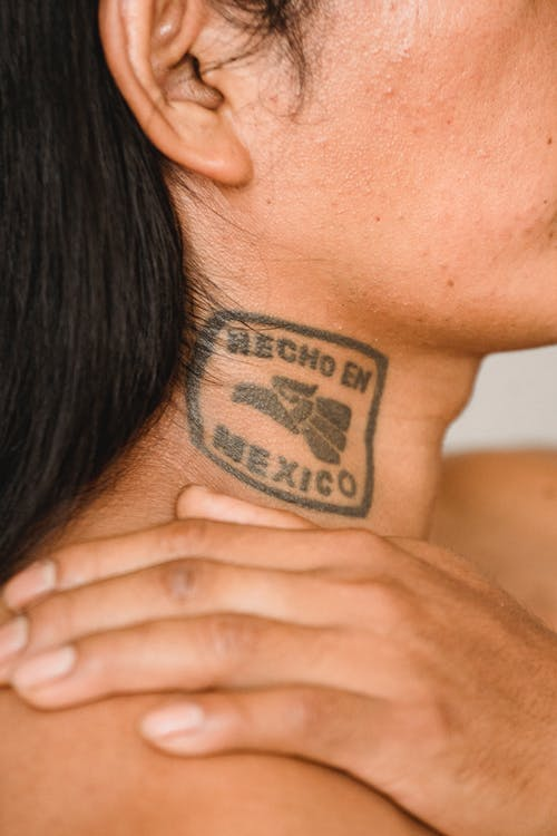 Crop anonymous ethnic man with long dark hair and tattoo on neck touching naked shoulder