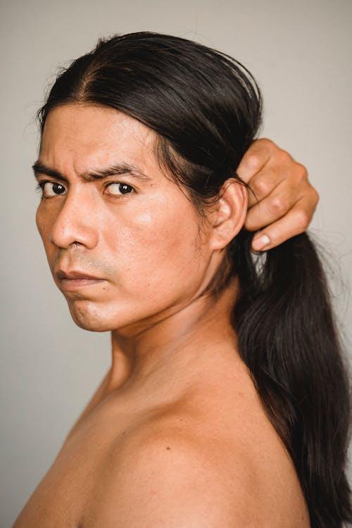 Ernstige Indiaanse Man Haar Aan Te Raken En Camera Te Kijken