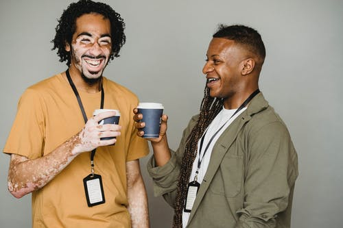 Cheerful black man with vitiligo skin laughing and drinking coffee with androgynous black man with afro braids against gray background