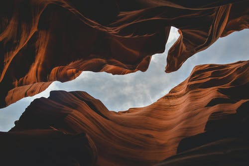 Brown Rock Formation Under White Clouds
