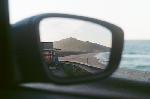 Car Side Mirror Showing Brown Concrete Building