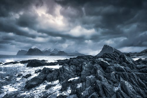 Stormy sea near rocks under cloudy sky in overcast weather