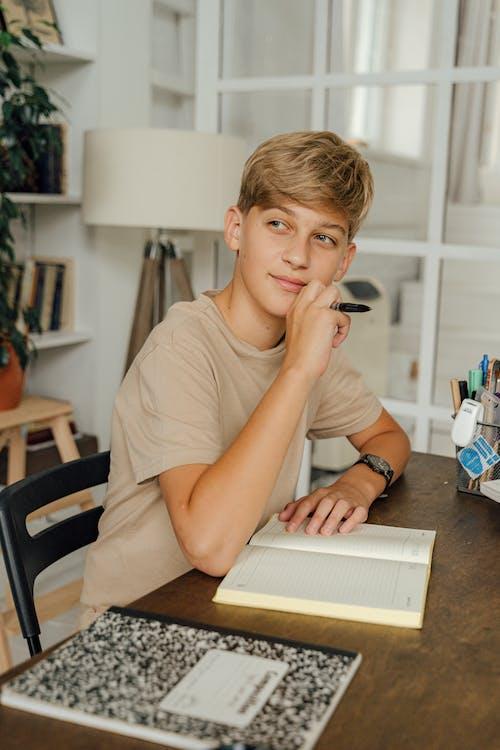 Boy in Brown Crew Neck T-shirt Sitting on Chair