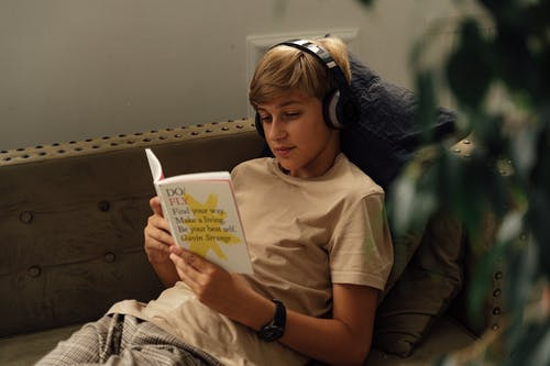 A Boy Reading a Book while Listening to Music