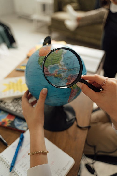 Person Using a Magnifying Glass to Look into the Globe