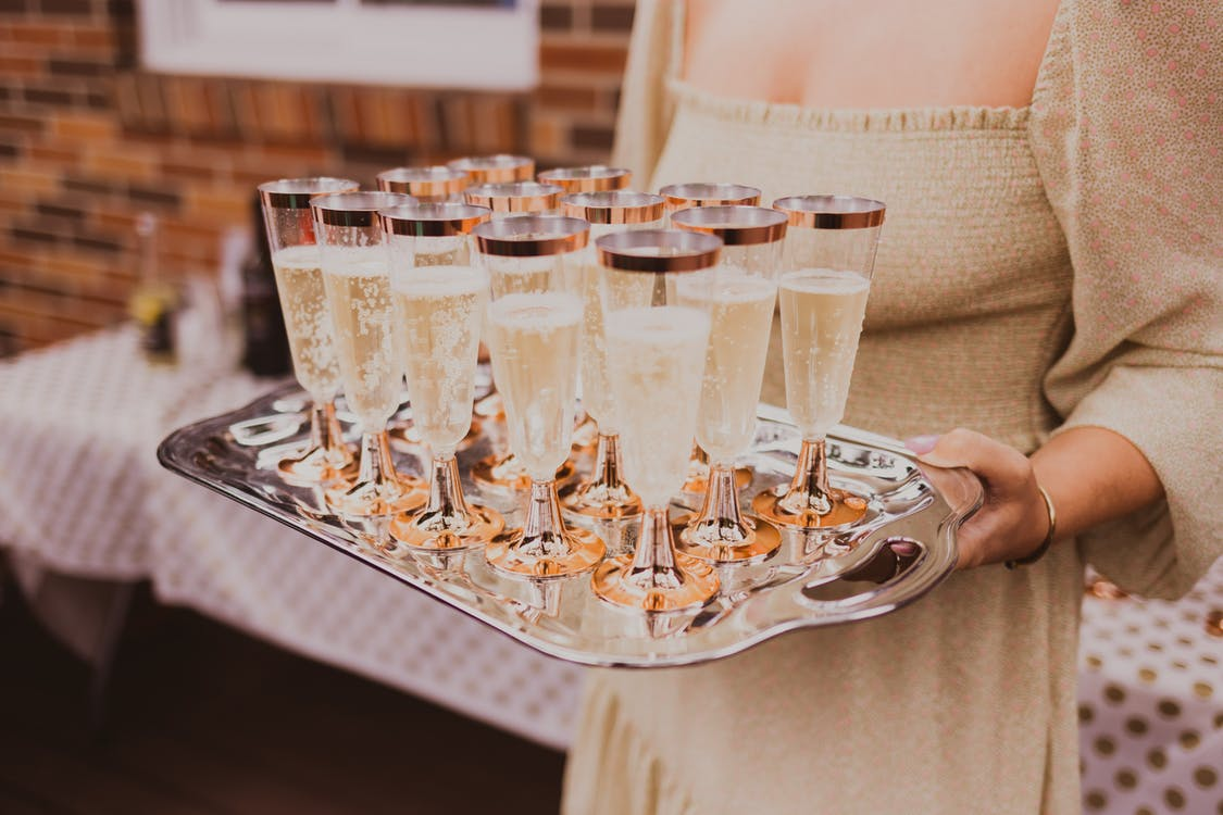 Crop woman with tray of champagne glasses