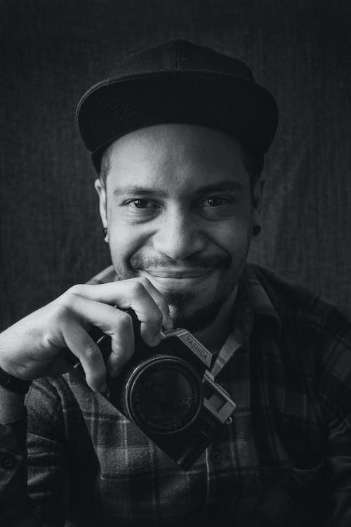 Black and white of self assured young ethnic bearded guy in stylish checkered shirt and hat smiling while taking photos on vintage camera in studio