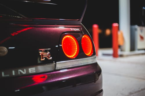 Bright taillights of luxury auto in gas station