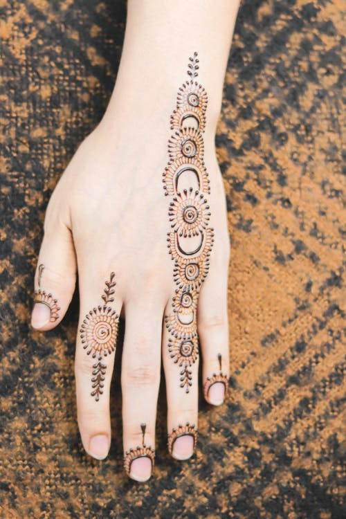 Person With Black and Silver Floral Hand Tattoo