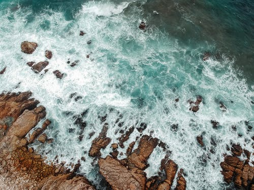 From above of foamy ocean with turquoise water washing rocky shore in daytime