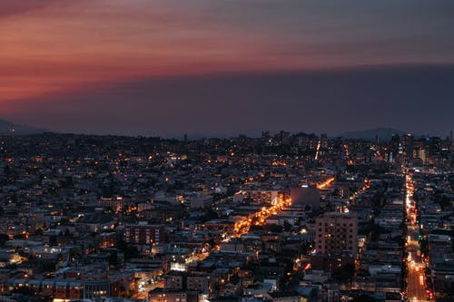 Aerial view of illuminated city district with busy highway at night under bright sunset sky