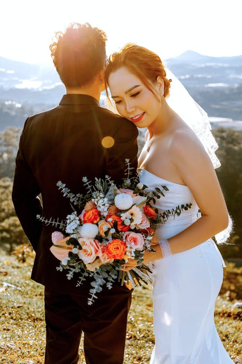 Loving ethnic bride with fiance standing together on hill