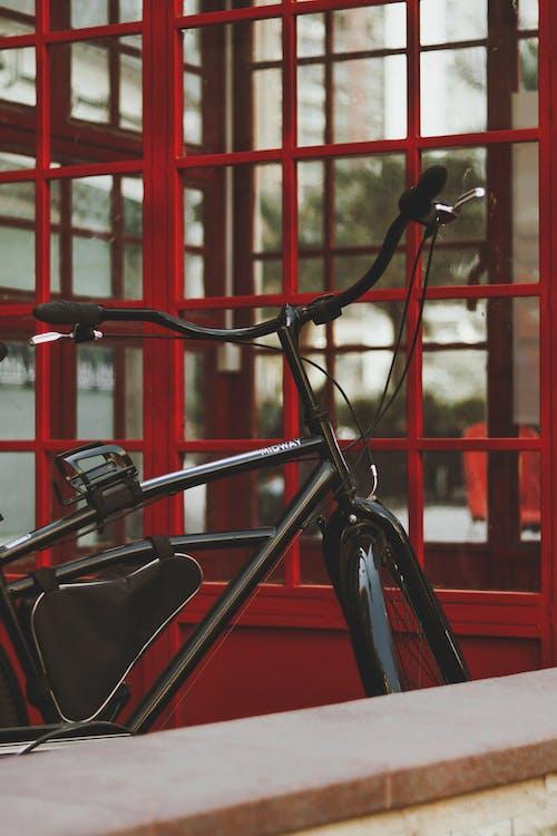Black and Red Bicycle Beside Red Metal Railings