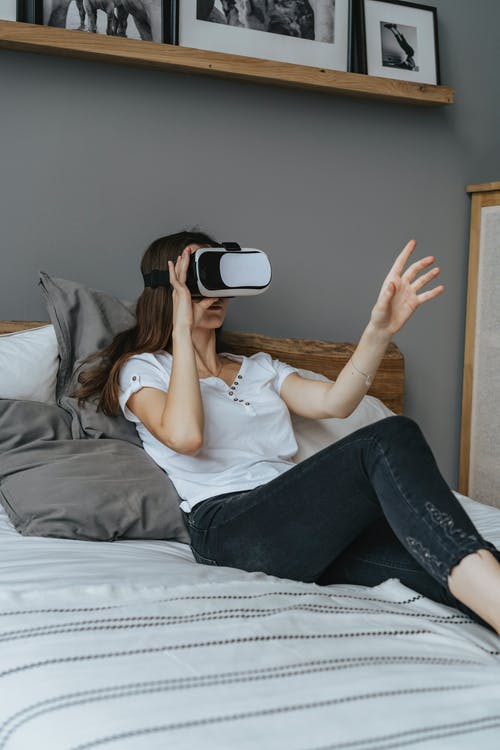 Woman Sitting on the Bed Wearing a Virtual Reality Googles