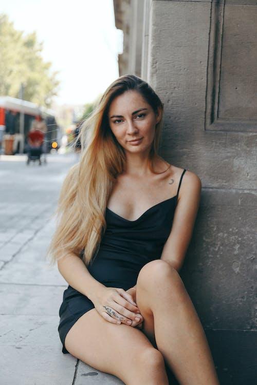 Woman in Black Spaghetti Strap Top Sitting on Gray Concrete Wall