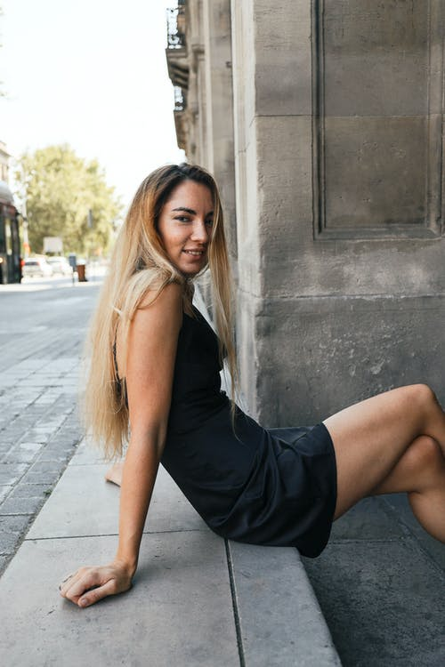 Woman in Black Tank Top and Black Skirt Sitting on Gray Concrete Wall