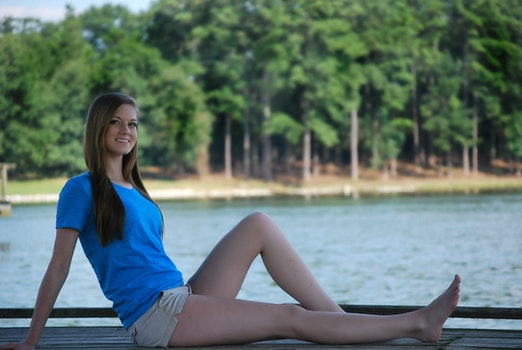 Woman Wearing Blue T Shirt and Beige Short Sitting on Brown Wooden Panel Near Body of Water during Daytime
