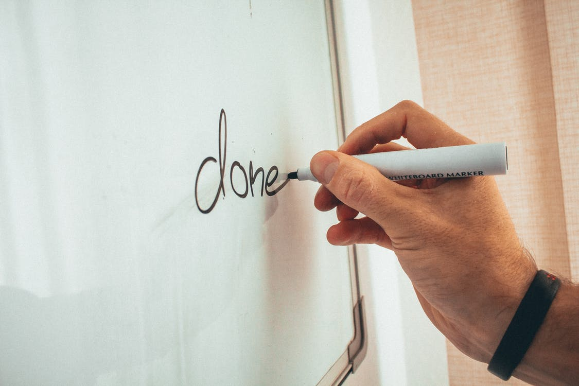 Crop unrecognizable male coach writing done word on whiteboard during presentation in light office