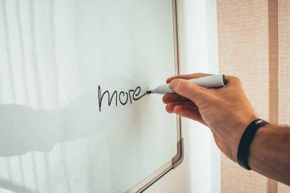 Crop unrecognizable man writing more word with marker on whiteboard during creating new startup in light workplace