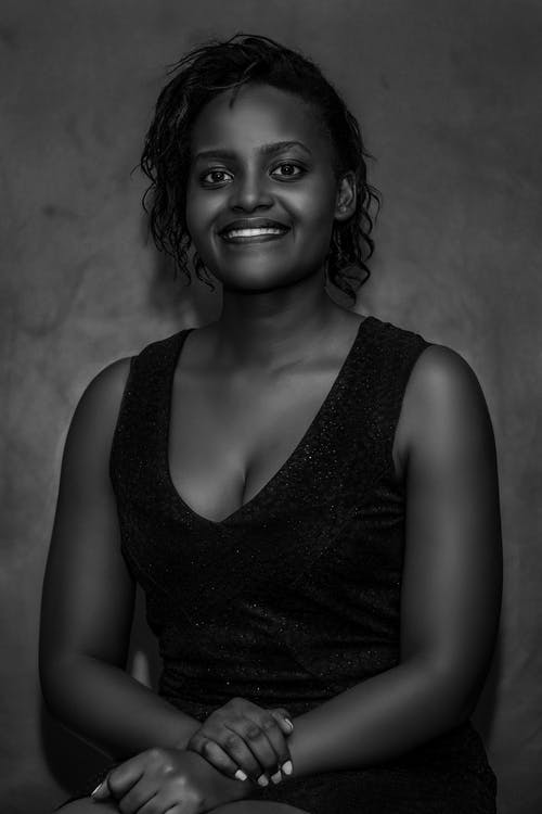 Black and white positive African American female with toothy smile in elegant dress sitting with crossed hands