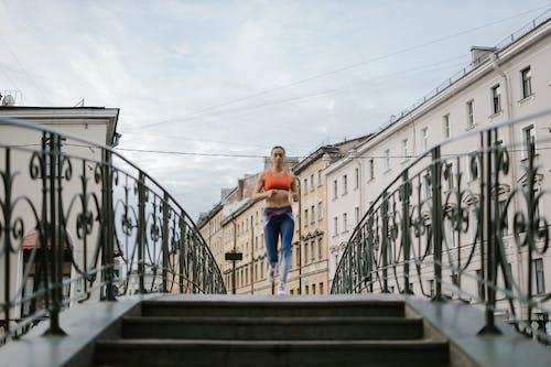Woman in Orange Tank Top Running on a Walk Bridge