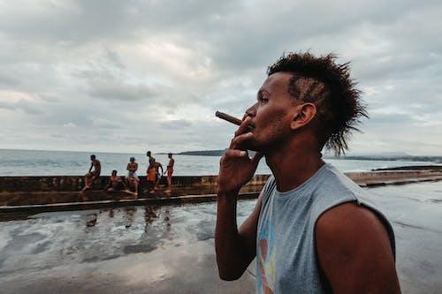 Ethnic man smoking cigarette on embankment