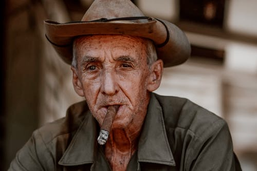 Elderly man in hat smoking cigar