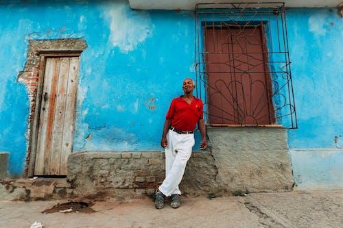 Ethnic man standing near shabby house