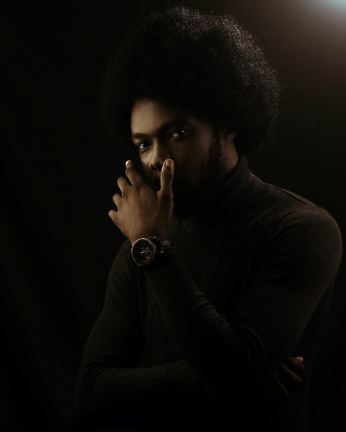 Young serious bearded African American male with curly hair keeping hand near face while thoughtfully looking at camera