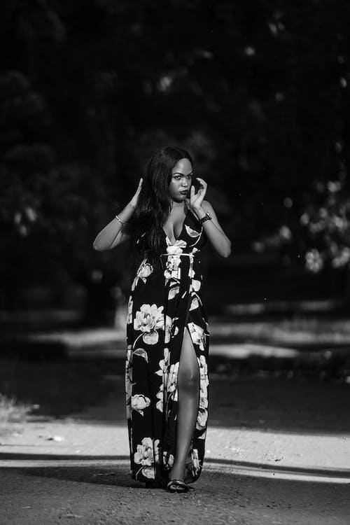 Elegant black woman in long dress walking in park