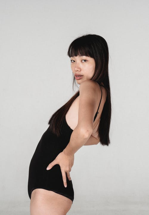 Side view attractive Asian female model in black bodysuit standing with hands on waist and bending back slightly while looking at camera in light studio