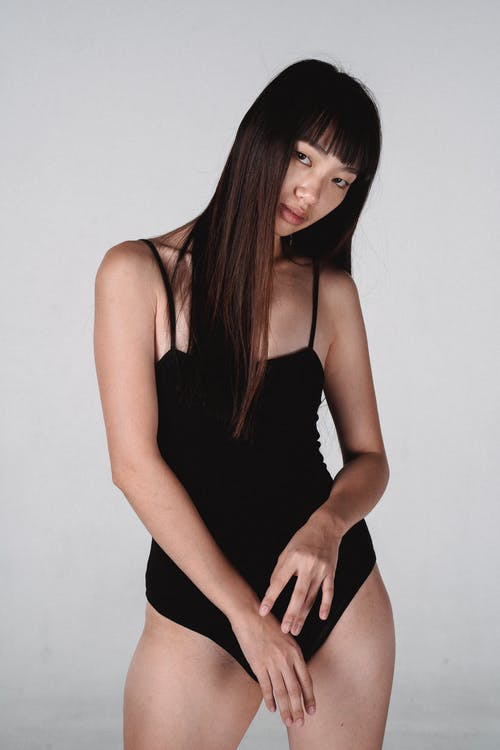 Young pretty Asian female model wearing tight black bodysuit standing on white background and looking at camera contentedly