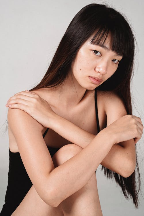 Wistful Asian woman sitting against white background in studio