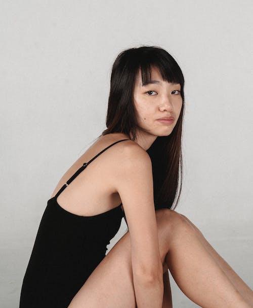 Bình Tĩnh Trẻ Châu á Phụ Nữ Mặc Bodysuit Ngồi Trong Phòng Thu Màu Xám