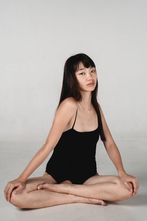 Graceful young ethnic woman sitting on floor with crossed legs in studio