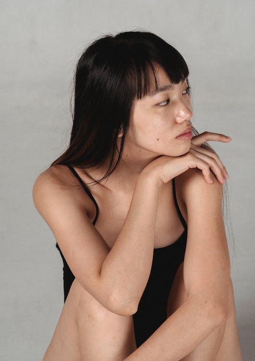 Dreamy ethnic woman in lingerie near wall