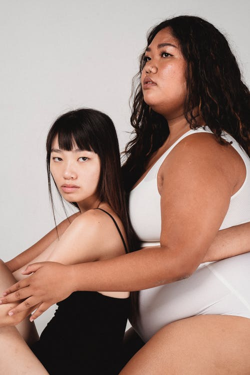Side view of  young slim and overweight Asian female models with dark hair in bodysuits embracing against gray background