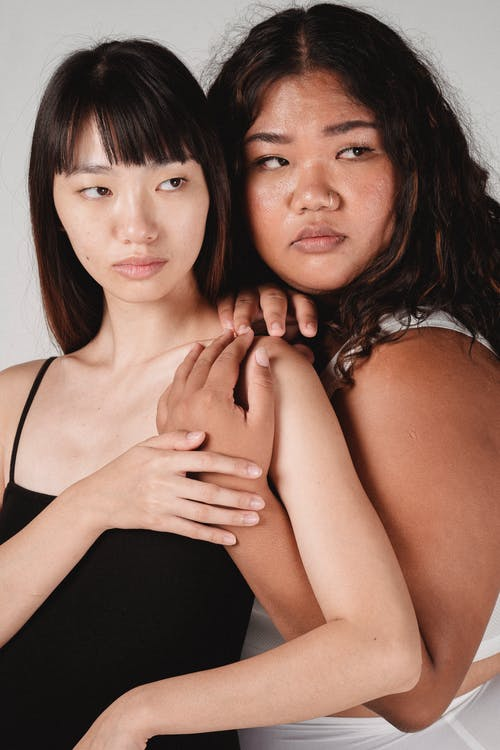Graceful young ethnic ladies hugging and looking away
