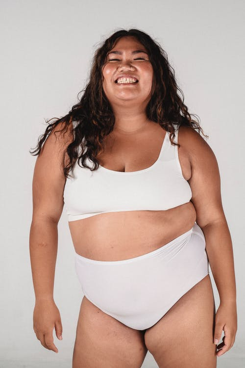 Overweight happy Asian woman with toothy smile