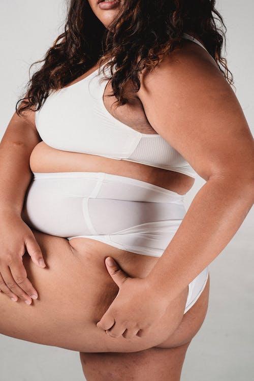 Overweight woman in underwear touching buttocks