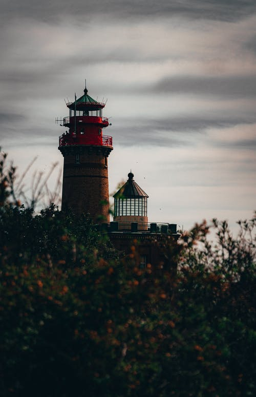 Red and White Lighthouse Near Green Trees Under Cloudy Sky