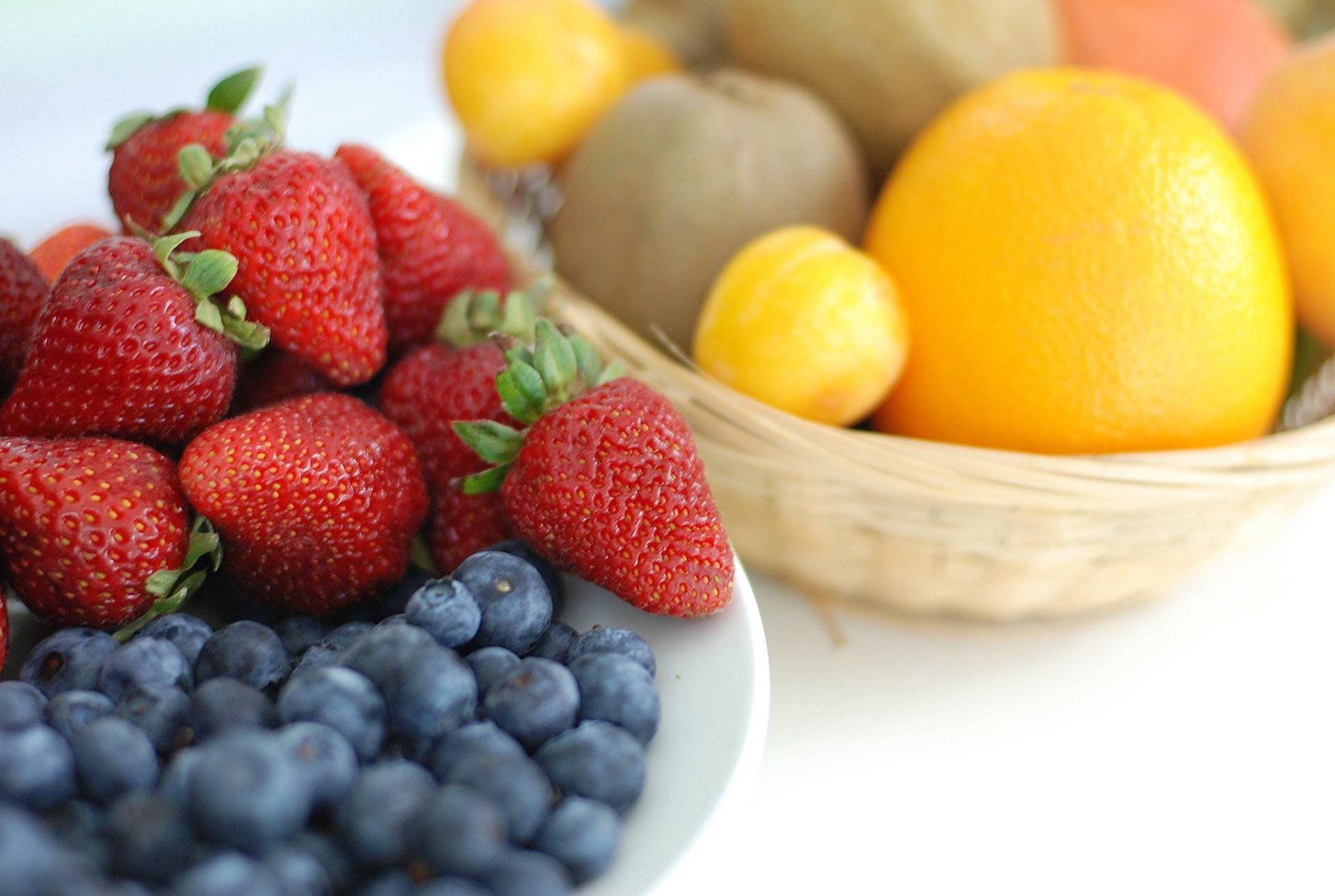 Red Strawberry, Blue Berry on White Plate Near Brown Woven Basket